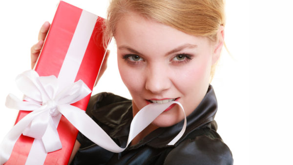 Young woman with wrapped gift, biting ribbon