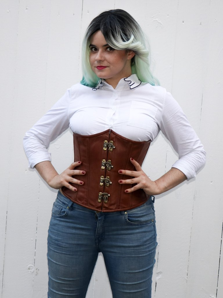Delilah Dentata in the Cersei Underbust Corset in natural brown leather with jeans and button-down shirt