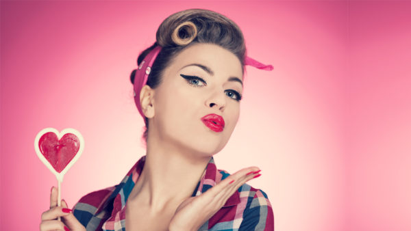 Retro girl blowing kiss while holding heart-shaped lollipop against pink background